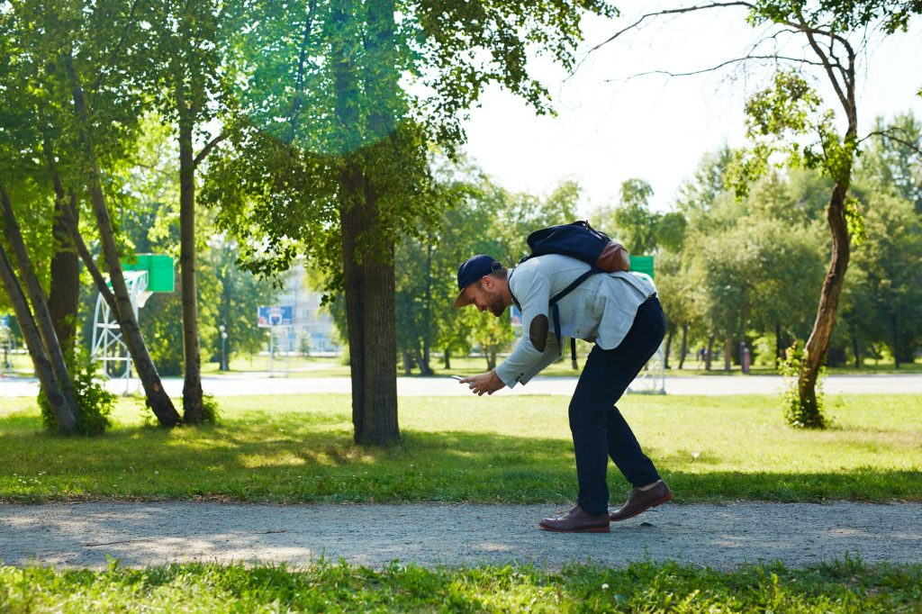Mies pelaamassa ulkona mobiilipeliä