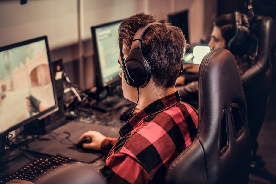 Pelaaja istuu pelituolissa pelaamassa